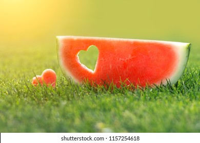 Watermelon slice with a heart shaped cut on the grass
