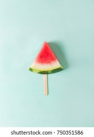 Watermelon slice on a stick on a  turquoise background.