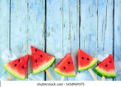 Watermelon slice popsicles against a rustic blue wood background forming a bottom border