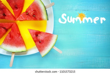 Watermelon slice popsicles on yellow plate on blue turquoise wooden rustic background and inscription summer, top view, copy space.