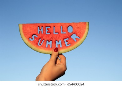 Watermelon slice  with text Hello Summer,  woman hands holding it against blue sky. Summertime concept.