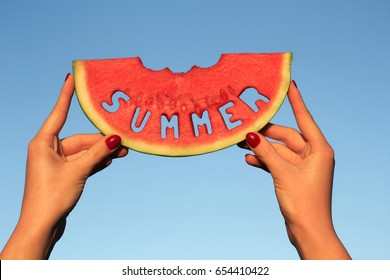Watermelon slice with text Summer, woman hands holding it  against blue sky. Summertime, watermelon lover, summer sale concept.