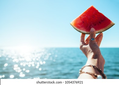 Watermelon slice in woman hand over sea - POV. Summer beach concept. Tropical fruit diet.