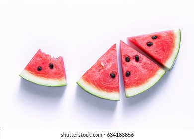 Watermelon sliced into a slice of wood on an white background.