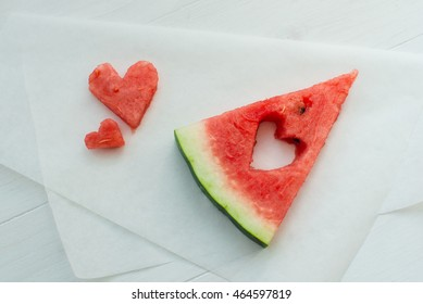 Watermelon with slices in the form of hearts on baking paper on a white wooden table