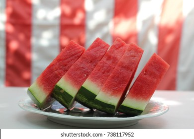 Watermelon slices in front of United States flag, outside at a summer barbecue, as for Memorial Day or the Fourth of July / Independence Day.