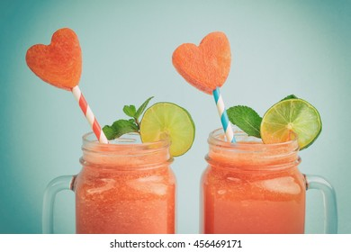 Watermelon smoothie in Mason jars decorated with mint, lime and watermelon slices curved like heart symbols
