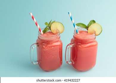 Watermelon smoothie in Mason jars with lime and mint on blue background