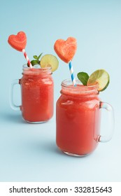Watermelon smoothie in mason jars for Valentines Day. Watermelon shake decorated with lime, mint and heart shaped watermelon slices on blue background