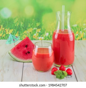 Watermelon smoothie with strawberries and mint on a wooden table, close-up side view.