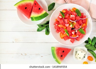 Watermelon and tomato salad with feta cheese. Top view, corner border on a white wood background with copy space.