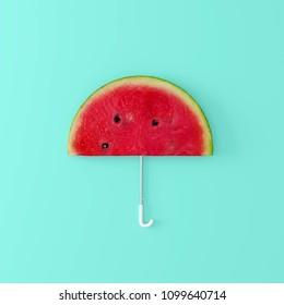 Watermelon umbrella on pastel blue background. Creative idea. minimal concept