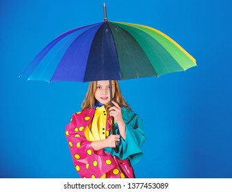 Waterproof accessories manufacture. Enjoy rainy weather with proper garments. Waterproof accessories make rainy day cheerful and pleasant. Kid girl happy hold colorful umbrella wear waterproof cloak.