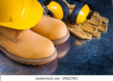 Waterproof boots leather protective gloves earmuffs and building helmet on scratched metallic background construction concept.