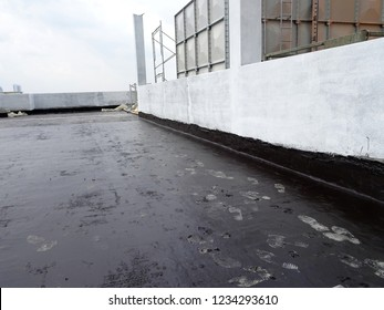 Waterproof coatings applied on flat roof concrete surfaces. There are several layers and layers of fiber mesh added to strengthen the bonding of the waterproofing layer.