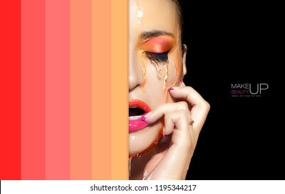 Waterproof makeup concept. Sensual young woman with unblemished skin, bright make-up and orange liquid streaming down half of her face. High fashion beauty portrait on black background. Color ecstasy