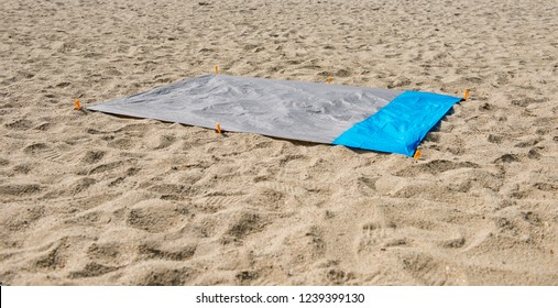 Waterproof and sandproof nylon beach blanket on sand. Very thin tarp or footprint used for outdoor activities, as a barrier agains the sand or ground, keeps you dry and clean.