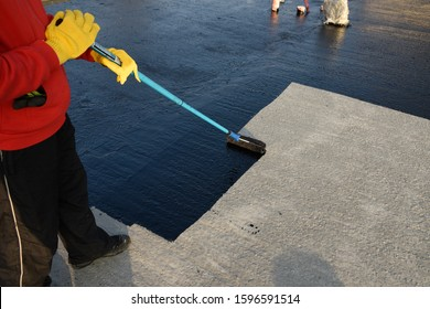 Waterproofing coating. Worker applies bitumen mastic on the foundation. Roofer cover the rooftop polymer modified bitumen waterproofing primer, with a roller brush.