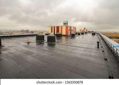 Waterproofing the roof of residential building. Covering roofing material. flat roof with roofing and fencing.