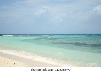 The waters of a tropical beach range from aqua to dark blue. The sand is pale gold. Storm clouds are massing on the horizon.