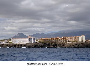 Waterside distant view coastline of Costa del Silencio during stormy weather, moody cloudscape above the town, Tenerife, Atlantic Ocean, Spain