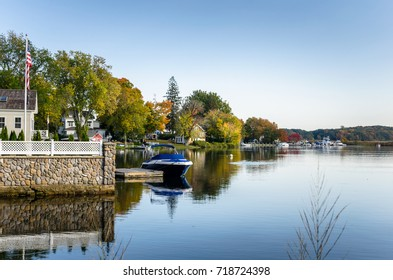Waterside Houses among Trees with Boats Moored to Wooden Jetties on a Clear Autumn Day. Connecticut River, Essex, CT.