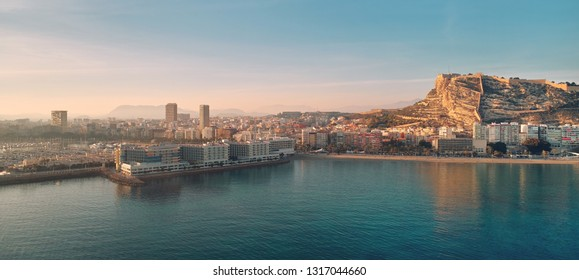 Waterside panoramic view clear blue sky, turquoise bay of Mediterranean Sea, castle of Santa Barbara in tourist resort town Alicante south of Spain, Costa Blanca, copy space for text