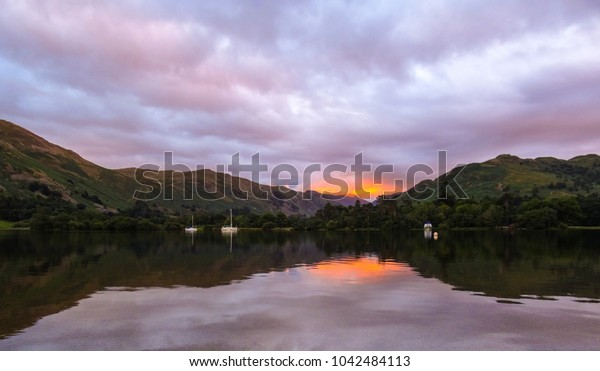a waterside view of a sunset with cloudy skies