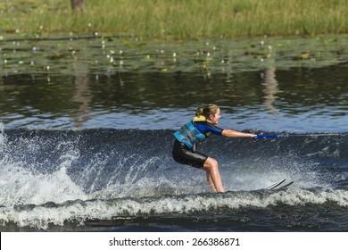 Water-Sking Girl  Young teen girl  water-skiing on rural mountain lake waters during summer season.