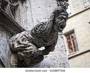 A waterspout gargoyle representing a witch on the building facade of the neo-Gothic courtyard of the city hall of Munich, Germany