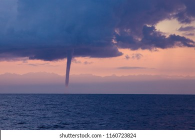 Waterspout (tornado) over the big lake. A huge column between cloud and body of water is clearly visible. Kyrgyzstan, Issyk-Kul Lake.