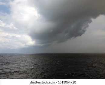 Waterspouts form at the far end of dark rain clouds