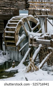 Waterwheel of old watermill in Krasnikovo, Kursk region. Winter, watermill is frozen in ice, covered with Icicles