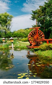 Waterwheel and pond with green trees at Semiwon garden in Yangpyeong, Korea