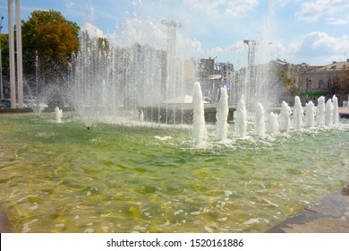 Waterworks fountain with water sprays and geysers on city park or street. Autumn day time freshness and relax concept. Clear aqua pool and yellow and red leaves trees