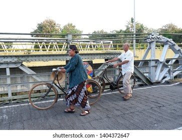 wates,kulon progo - may 19 2019 : men walking wearing javanese costume on the road with old roadster bicycle or pit onthel