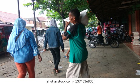 wates,yogyakarta-april 19 2019: javanese man holding bag of rice on his shoulder at local market,located in Pasar Wates Kulon Progo