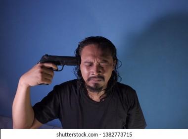 Wates,yogyakarta-april 28 2019: young man pointing gun on his head