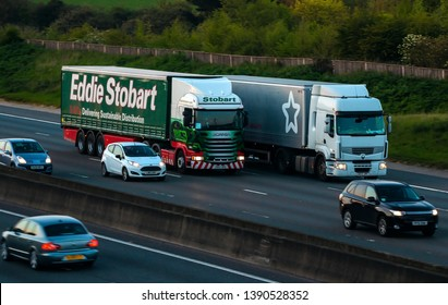 WATFORD, UK - APRIL 19, 2019: Evening traffic on British motorway M1. Eddie Stobard lorry on the road side by side with  Superdrug truck.