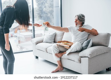 Wathing TV with scary woman with black hair near him. Senior stylish modern man with grey hair and beard indoors.