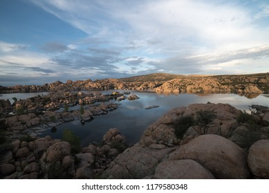 Watson Lake, Prescott Arizona. daytime with high white clouds reflecting in the lake water. shore line is made up of  large granite boulders.