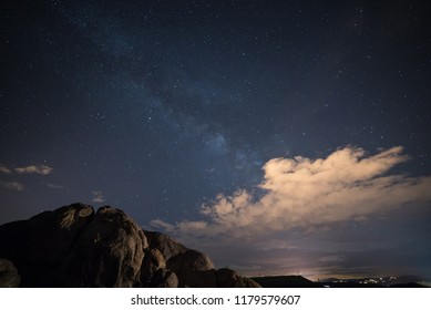 Watson Lake, Prescott Arizona. rock formations in the foreground and clouds with the milky way galaxy in the background.