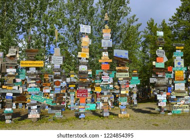 WATSON LAKE, YUKON, CANADA - JULY 19, 2018: The Sign Post Forest is the famous attraction of Watson Lake on the Alaska Highway. Travelers from all over the world bring signs and put them on poles