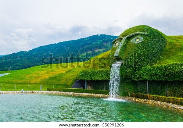 WATTENS, AUSTRIA, JULY 27, 2016: Fountain with giant head spitting water into a pond at swarovski Kristallwelten in Wattens, Austria.