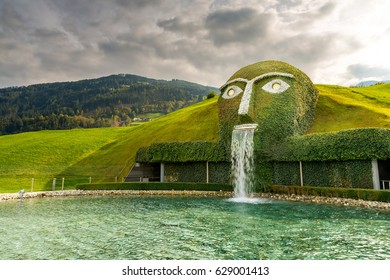 WATTENS/AUSTRIA-OCTOBER 10, 2015: Thematic centerpiece fountain with giant head art statue spitting water into green pond at Swarovski Crystal World glass museum exhibition center at Kristallwelten