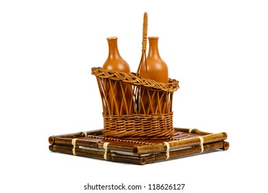 Wattled basket with ceramic wine bottles on a bamboo support