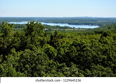 A Waukesha County Wisconsin lake seen from a high vantage point with the flat horizon in the distance.