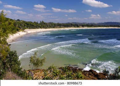 Wave after wave - an overlook of a curve beach and sea with white waves moving one by one towards the shore in a sunny day