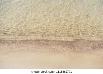 Wave of the Baltic sea on the white sand beach. Clear water, wavy sand seabed.