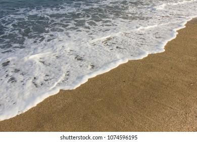 Wave of blue ocean on sandy beach